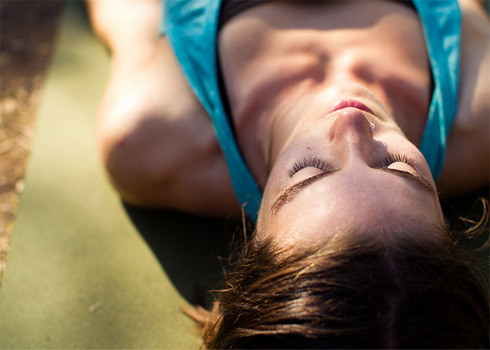 female lying down on yoga mat with filtered sunlight on her face