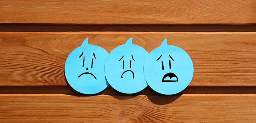 3 blue round stickies with hand drawn sad faces on them