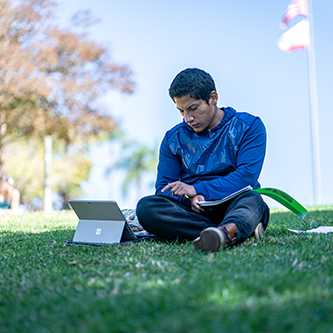 student studying with laptop in grass