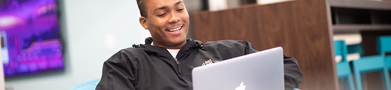 student with laptop sitting in comfy chair smiling