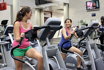 2 female students working out on stationary bikes