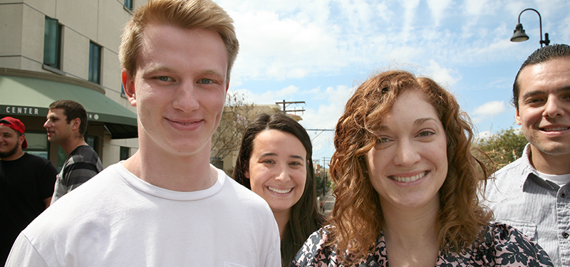 4 students smiling outside of Calpulli building with blue skies