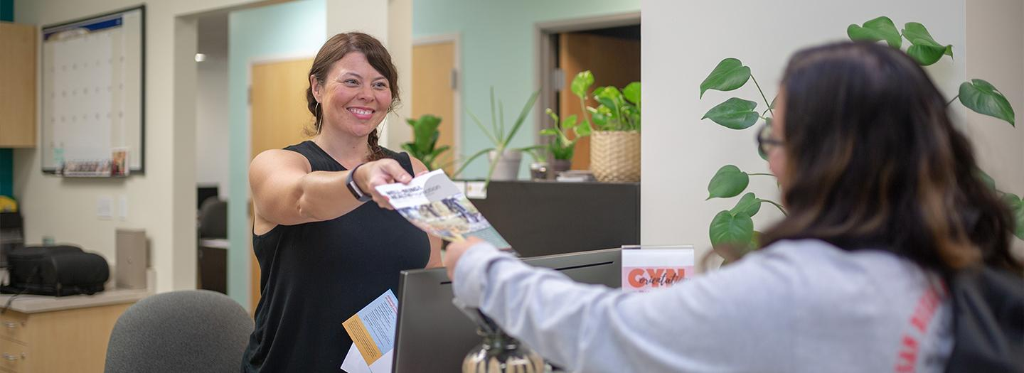 student receiving brochures at the front desk