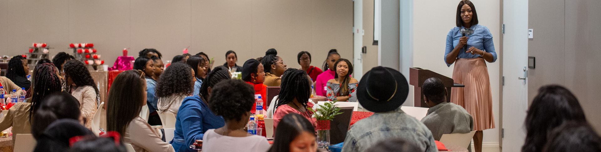 photo of sister to sister luncheon with large group of females sitting at tables listening to person presenting