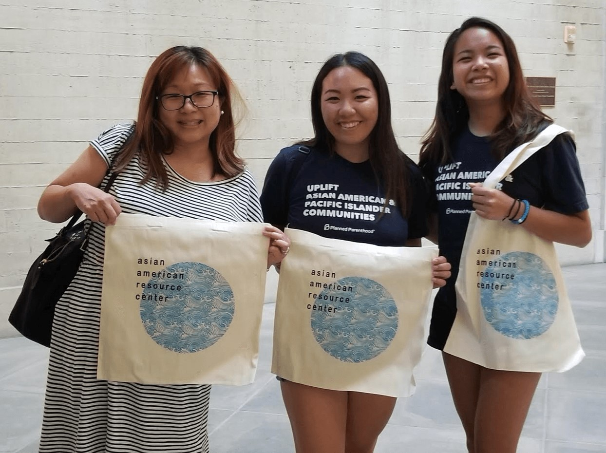group photo of 3 girls holding canvas apida bags