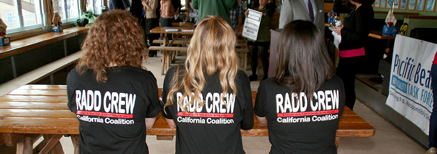 RADD crewin their matching black RADD crew california coaltions t-shirts, sitting at table in restaurant